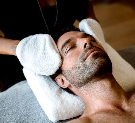Mann genießt Gesichtsbehandlung im Guerlain Spa Berlin